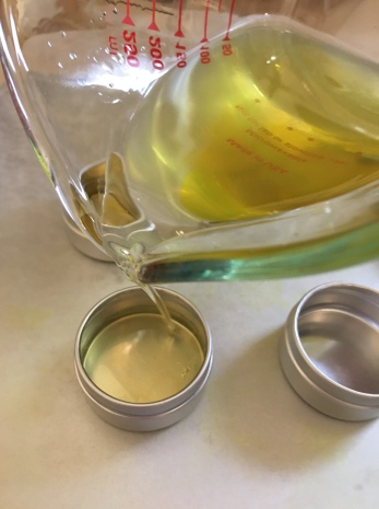 Pouring hot melted infused oils into tins.